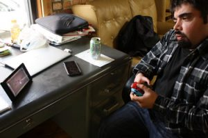 Michael Beers concentrates on playing the Switch using the adapted controllers. The switch screen is propped on its stand on his desk.