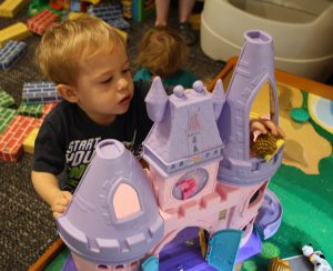Little guy dropping plastic animals off the balcony of a Fisher Price castle.