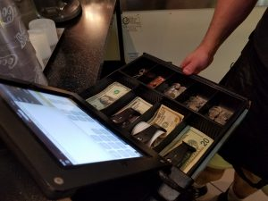 View of the cash drawer and the iPad Wilkins uses with the ShopKeep app.