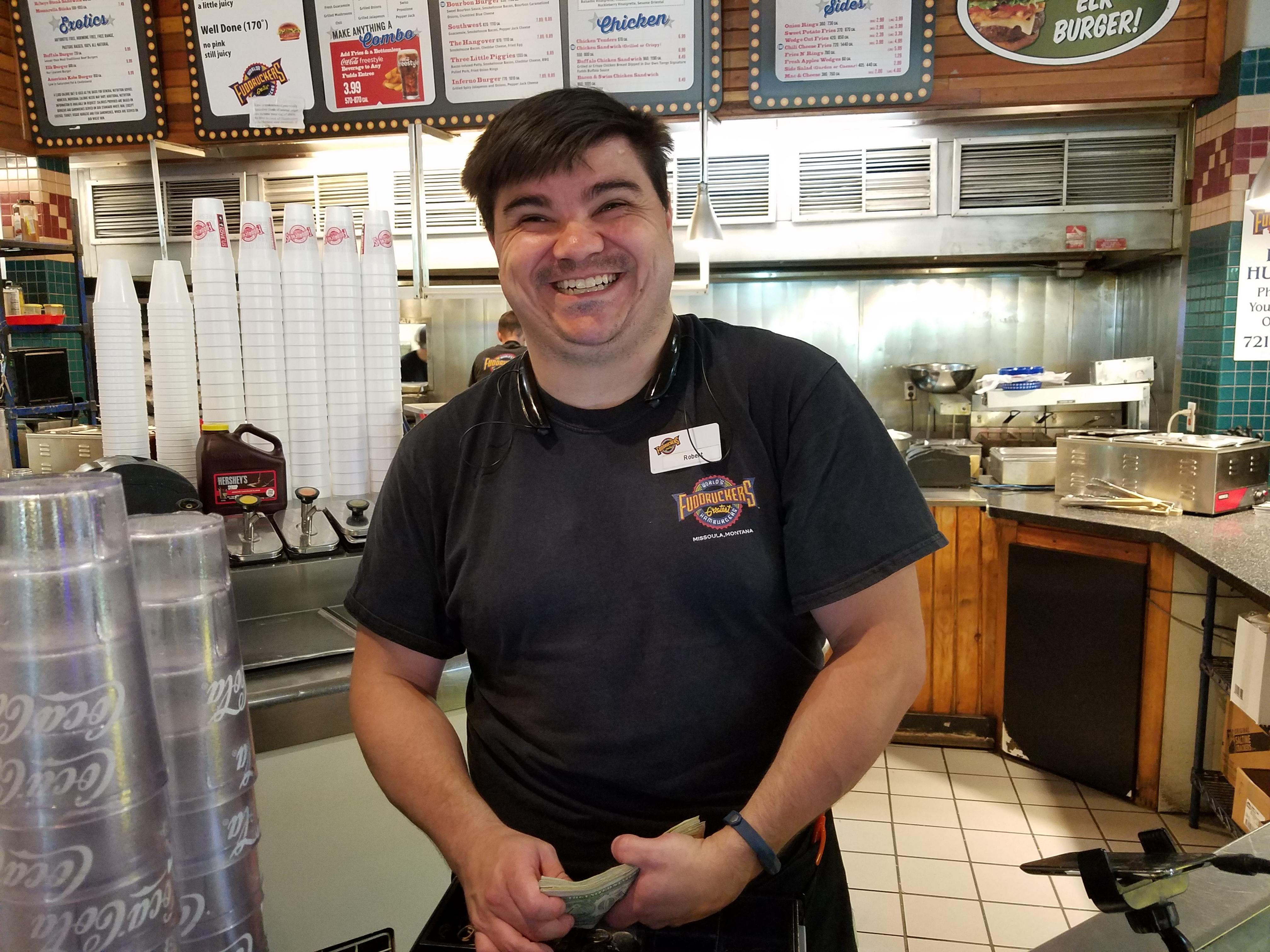 Robert Wilkins at the register in Fuddruckers, cash in hand.