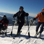 Sherene on top of Whitefish Mountain, flanked by Molly Blair on her left and a sit skiier on her right.