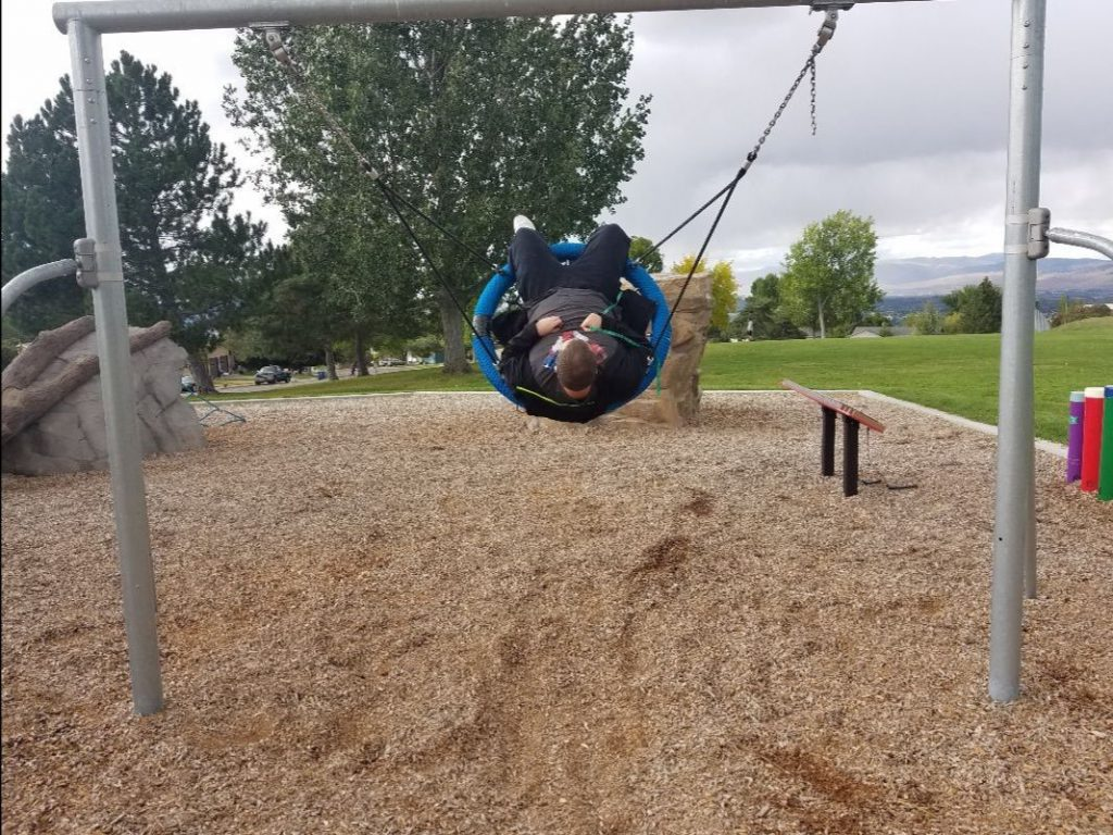 Young man swinging high in saucer-shaped swing.