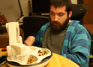 Devin waits while the Obi spoons up some trail mix. Obi is sleek, white design with robotic arm and four bowls set into a tray.