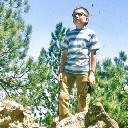 Doug Doty, as a child, stands on a rock in the woods.