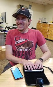 Ed, wearing a Where's Waldo T-shirt and dark cap, laughs while demonstrating a Braille display.