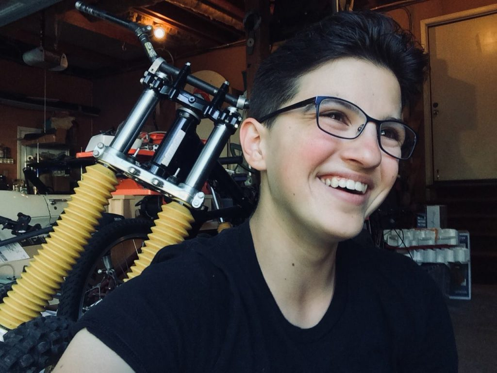 Eleni smiles, wearing black T, black rimmed glasses, short black hair. Customized bicycle in shop behind her.