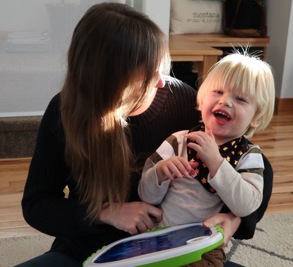 Rebecca, in dark sweater with long hair hanging over her face, holds a laughing Everett, the sunshine coming through a window onto his white-blond hair.