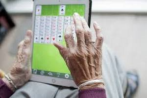 Older woman's hands playing solitaire on iPad.