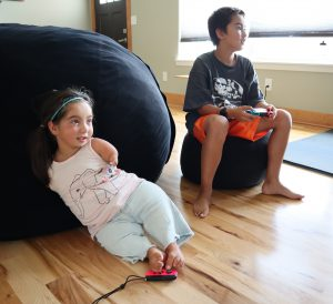 Tenley sits on the floor using her feet to control the Nintendo Switch while playing against brother Nathan, sitting beside her, holding his own switch controller in his hands.
