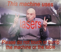"Sign posted on the MakerBot table showing Mike Myers as Dr. Evil, making air quotes as he says ""This machine uses lasers. Please do not touch or bump the machine or the table."""
