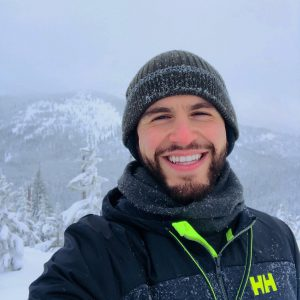 Hussam in winter hat and coat, smiling with a backdrop of mountains behind him