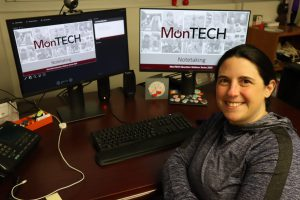 Michelle sits smiling at her desk with two computer monitors behind her showing a MonTECH Notetaking PowerPoint