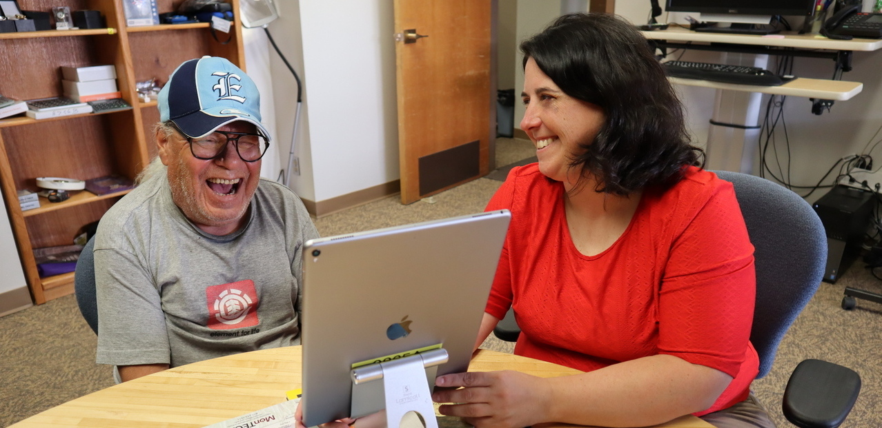 Michelle in red sweater, smiling, works with an iPad and an older man in blue cap, laughing hard.