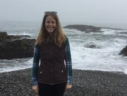 Kelsey Lastowski stands on a stormy, rocky beach.
