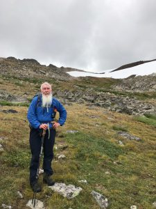 Rev. McCracken poses in a boulder field, a patch of snow behind him.