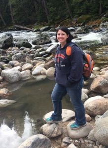 Michelle stands on rocks of creek bed near water, smiling and wearing orange back pack.