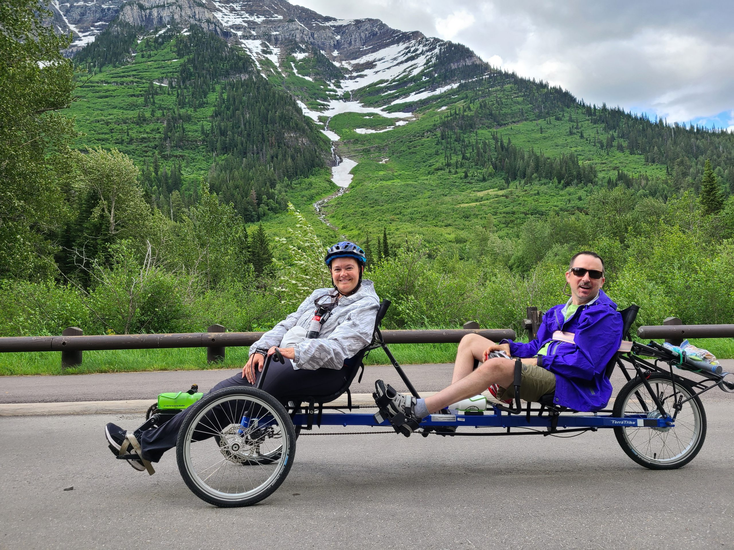 Peter and Sherene on the trike, a magnificent green, snow-capped mountain behind them