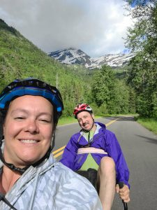 Sherene and Peter smile from their bike seats, a beautiful snowy mountain in the background.