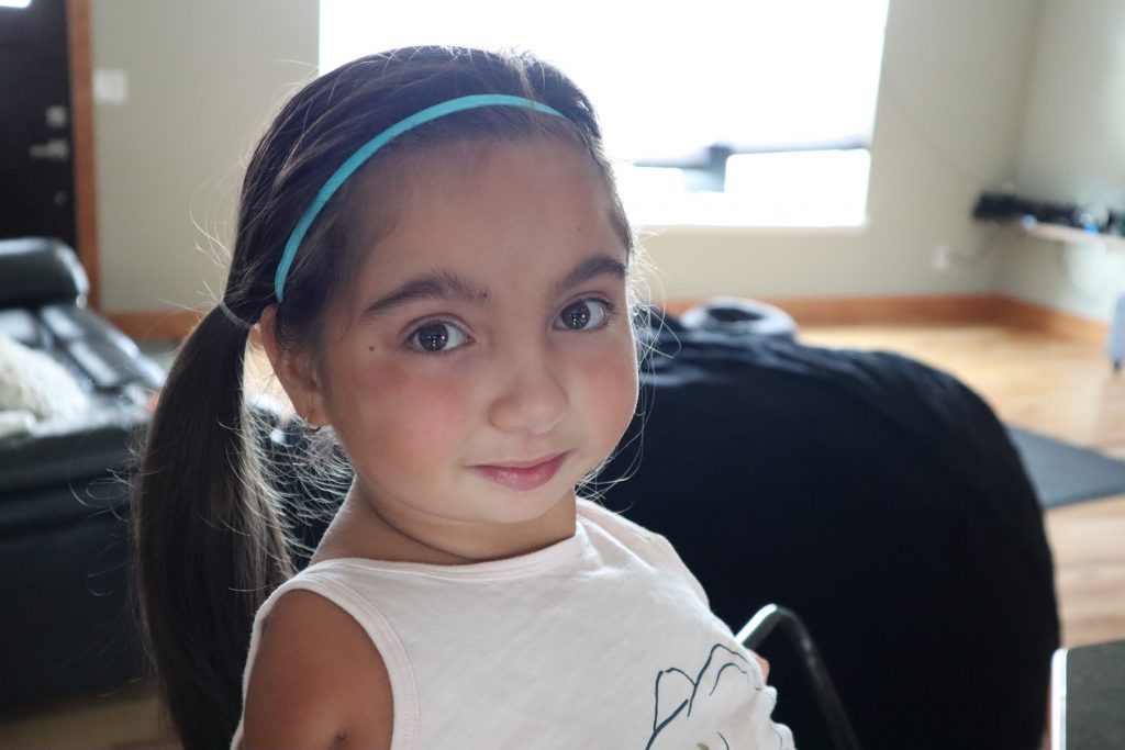 Close-up of Tenley's face. She is smiling, with big brown eyes, dark hair pulled back in ponytail, and a bright blue headband.