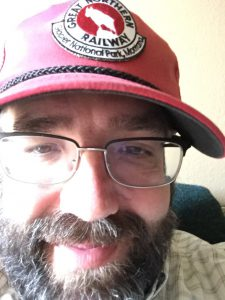 Extreme close-up of Tom with small smile, in red cap, glasses, and full beard and mustache.