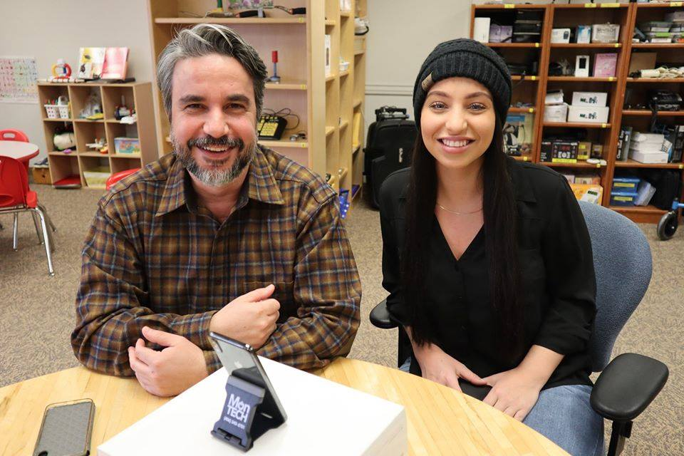 Wisam and author Alli sit side by side at table, smliing, with iPhone in front of them on a stand.