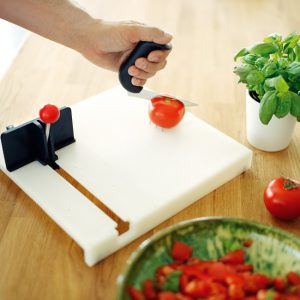 Person using food prep board to hold tomato for one-handed slicing.
