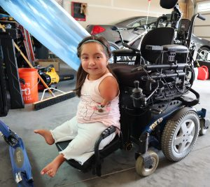 Tenley rides her vertical lift from her power chair's seat down to the floor.