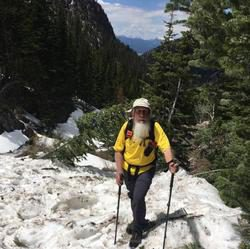 Rev. McCracken standing on a patch of snow high in the mountains in Yellowstone Park.