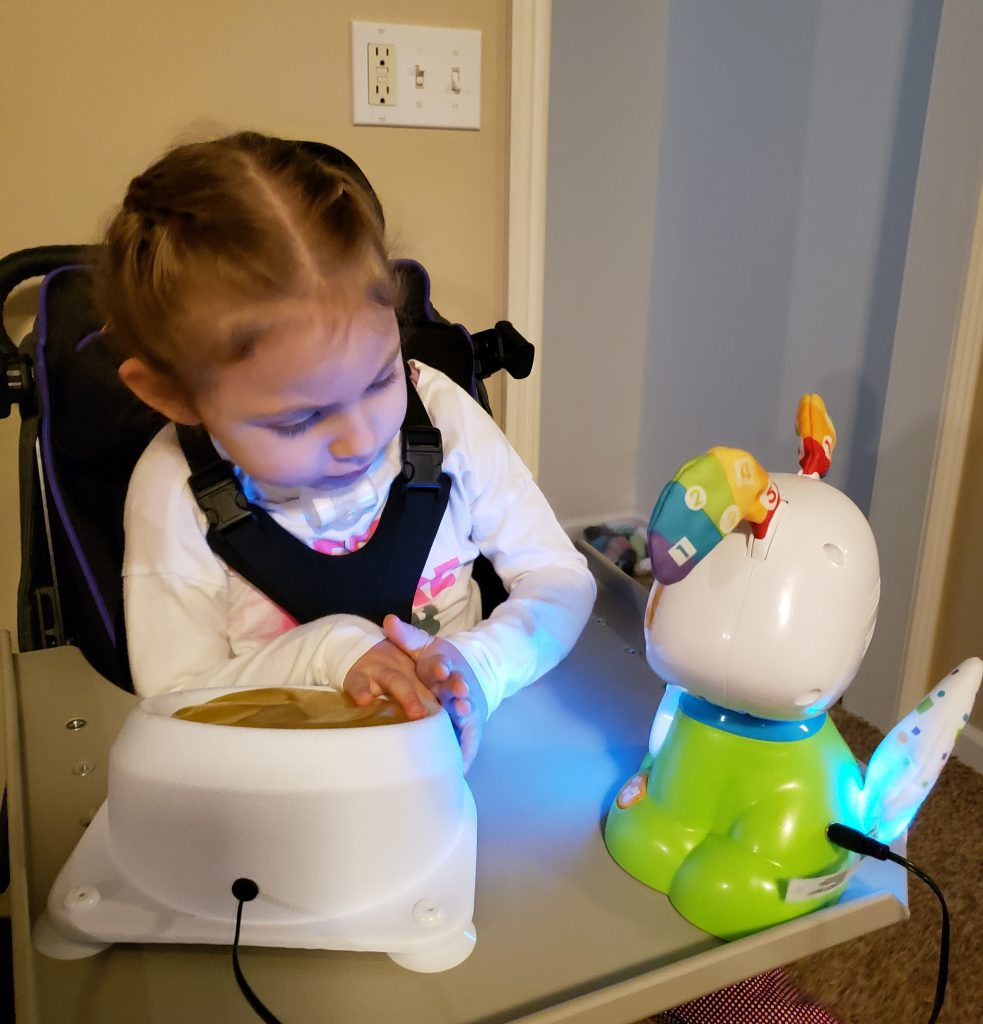 Kinsley sits at tray table and presses a switch to activate the toy she borrowed from MonTECH. Sweet looking little girl with hair in french braids.
