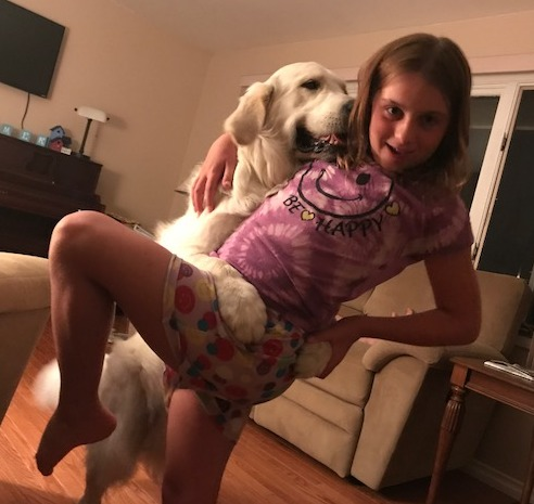 Olivia strikes a pose while dancing with cream retriever Chase in the living room.
