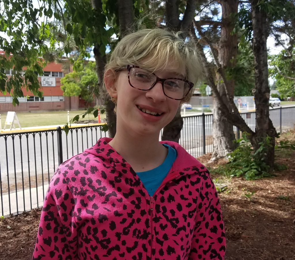 Sarah smiles at camera, wearing hot-pink leopard-spotted hoodie, black frame glasses, and short blond hair.