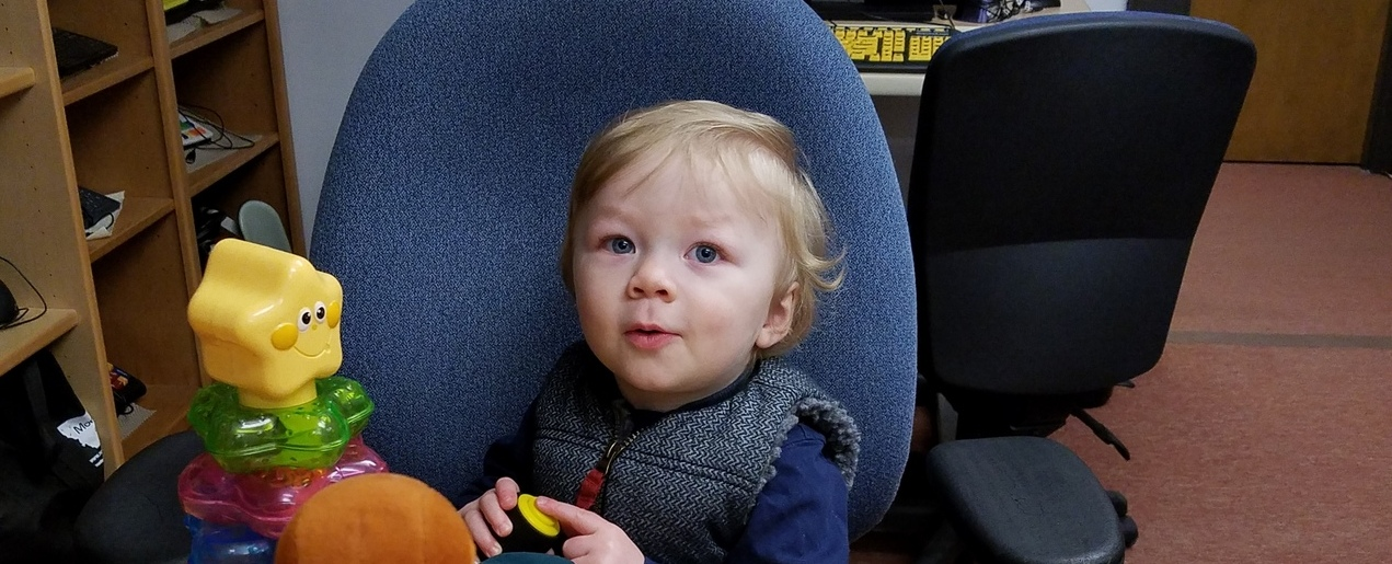 Two-year-old boy presses button to activate toy.