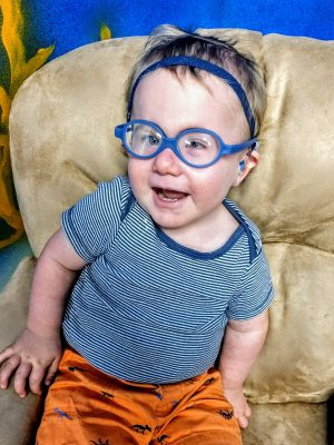 Caleb smiles at the camera, wearing blue plastic glasses, hearing aids on a blue headband, blue striped shirt and orange shorts.